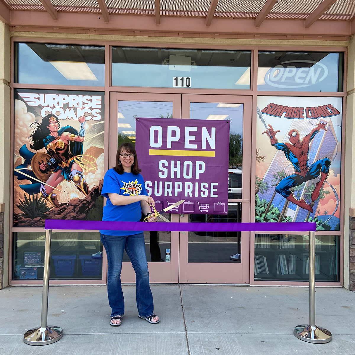 A purple ribbon is cut outside Surprise Comics for the business' re-opening.