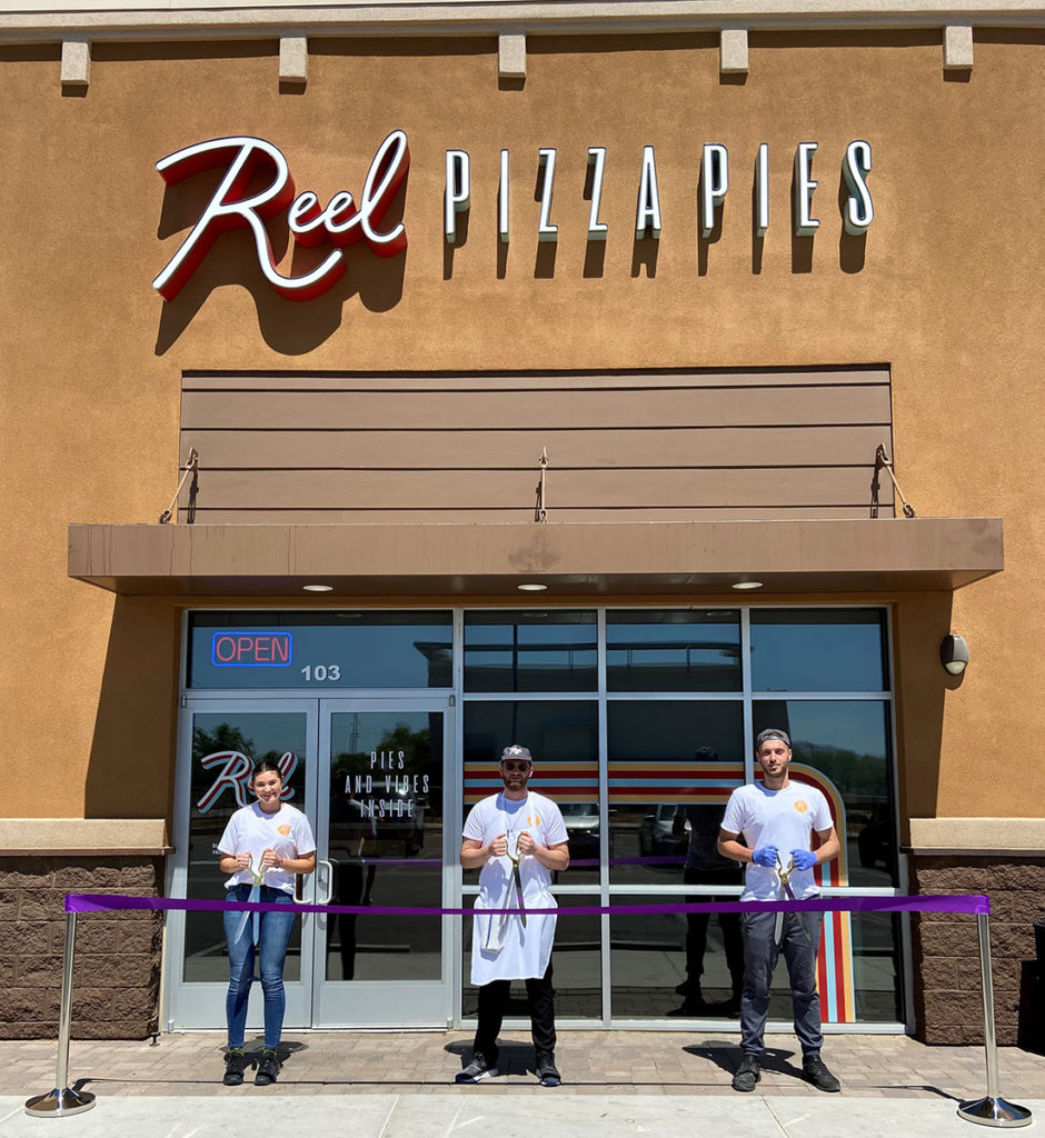 Three employees of Reel Pizza Pies hold scissors and stand behind a purple ribbon.