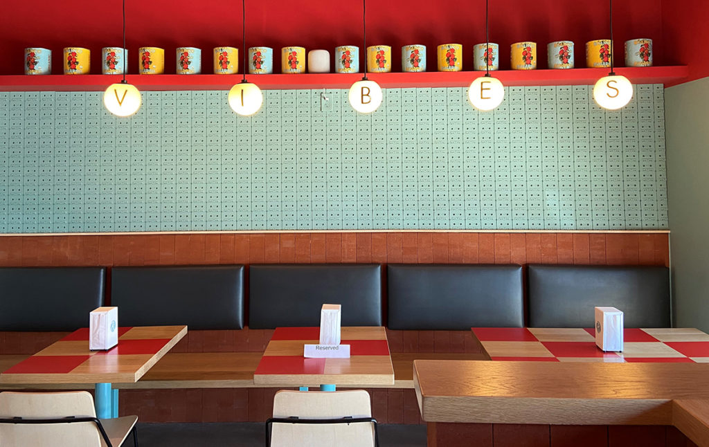 A seating area in the pizza parlor with red checkered table tops and hanging lights with letters that spell out vibes.