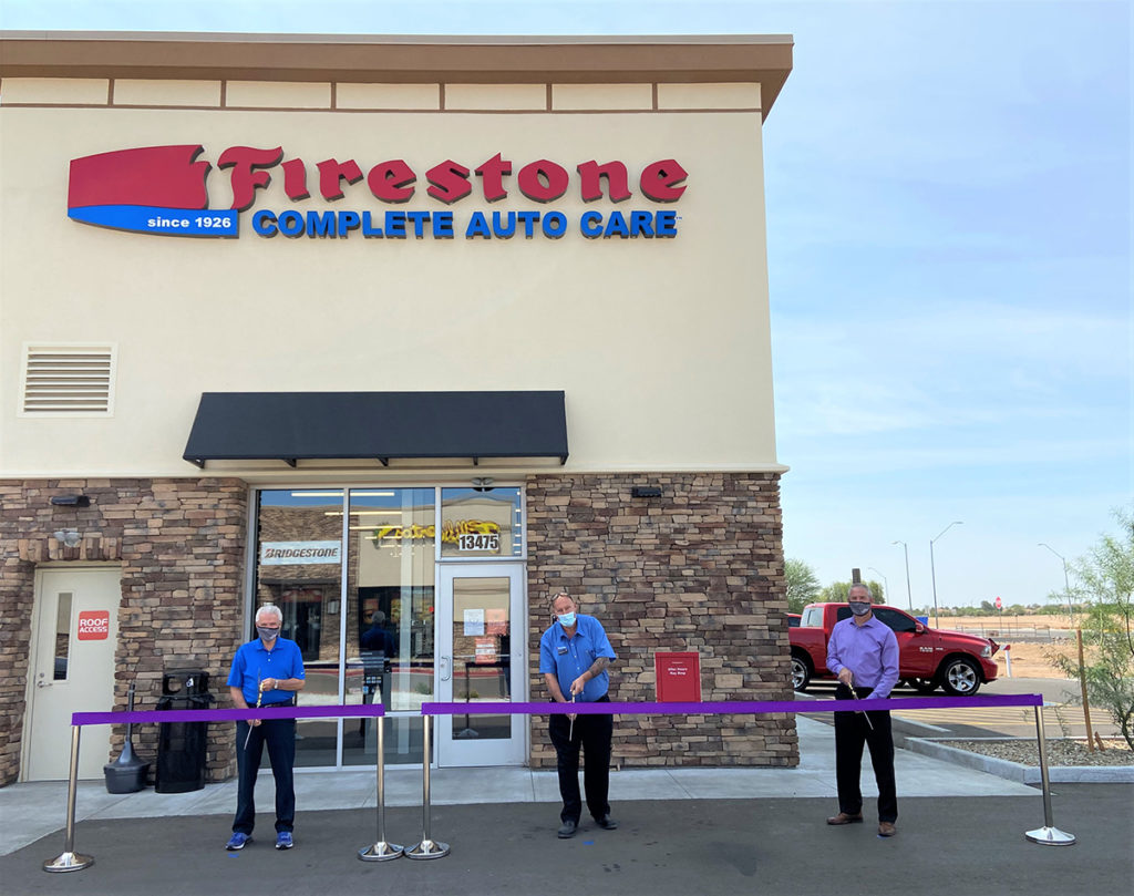 Mayor Hall and Vice Mayor Judd cut a purple ribbon outside of Firestone Complete Auto Care.