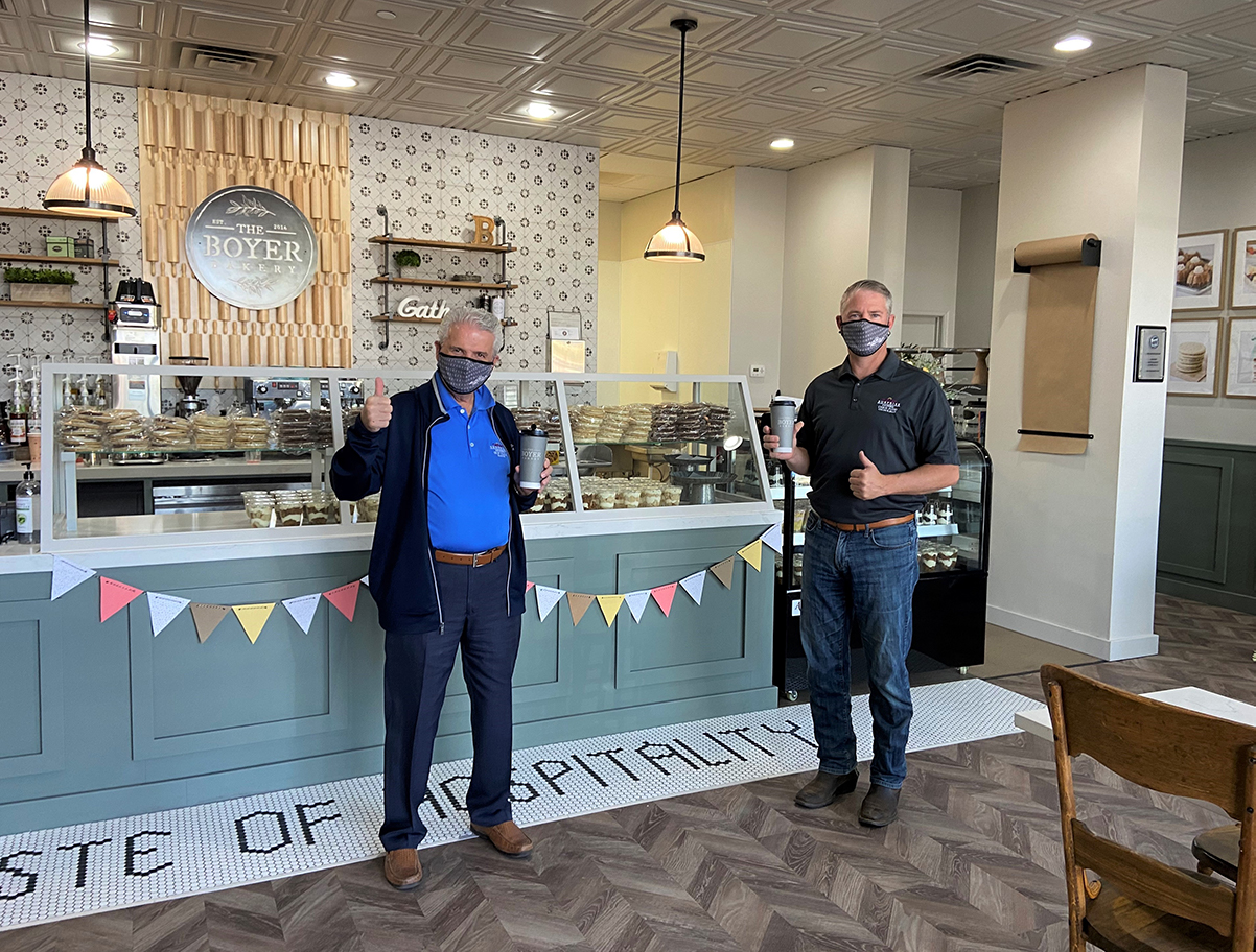 Mayor Hall and Councilmember Judd give thumbs up inside of The Boyer Bakery.
