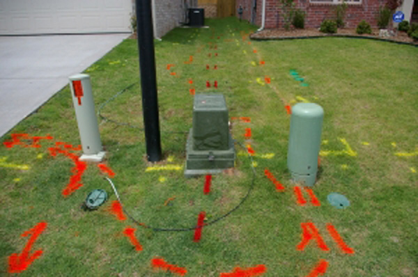 Grass is marked with red, yellow, and orange utility markings.